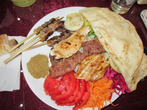 A mixed grill plate, with different types of meat all traditionally prepared