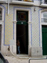 Someone doing some home repairs on an old-school, tile front, typical Lisbon building
