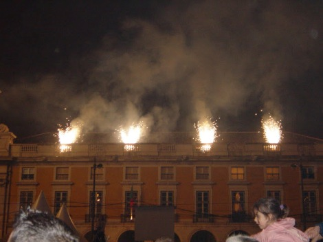 Fireworks being set off from the roof of a building adjacent to the square